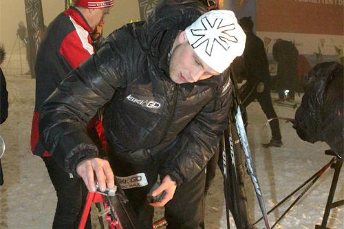 Henrik H. Kvissel jobber for fullt med å gi folk godt feste og topp glid på OBIK SkiGo karusellen. Her får Håvard Udnesseter (i bakgrunnen) hjelp med skiene. Foto: Erik Borg.