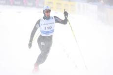 Anders Tettli Rennemo krysser målstreken i et inferno av snøføyke. For løperen fra Leksvik IL og Team Trøndelag ble det 7. plass på 15 km NM 2012. Foto: Geir Nilsen/Langrenn.com.