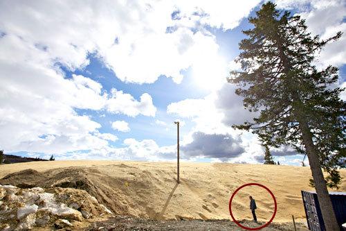 Erik Østli står her (inne i røde ringen) og beskuer det store deponiet av kunstsnø de har laget på Beitostølen. Foto: Nicolay Flaaten.