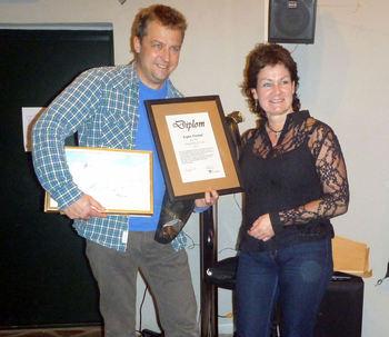 Anne Lise Marstein deler ut diplom og måleriet «Hestbrepiggane» av Wilhelm Bjertnes til Espen Finstad.