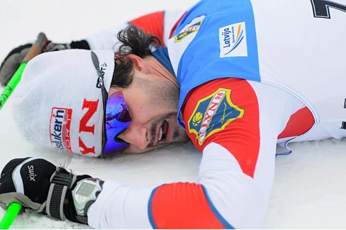 Hans Christer Holund har gitt alt og sikret seieren på 10 km i Skandinavisk Cup i Latvia. Foto: Martins Brize/Latvian Ski Association.