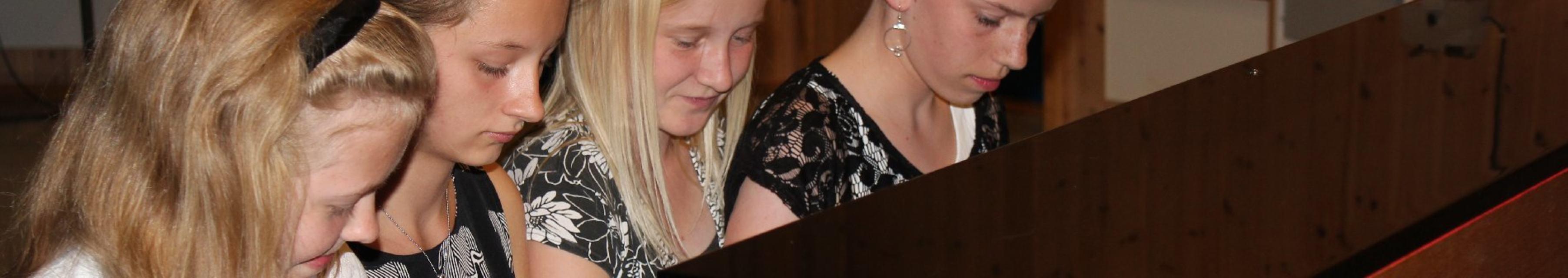 Fire dyktige jenter spiller sammen under en konsert i kulturskolen