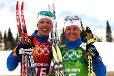 Iivo Niskanen, til venstre, og Sami Jauhojärvi smiler etter at Finland kapret gullmedaljen i lagsprinten under Sotsji-OL 2014. Foto: NordicFocus.
