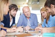 5 personer rundt et møtebord
