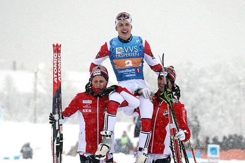 Simen Hegstad Krüger bæres på gullstol av lagkameratene Jonas Udjus Frorud (t.v.) og Hans Christer Holund etter at Lyn Ski ble norgesmestere på stafett i det tette snødrevet under NM i Tromsø 2016. Foto: Erik Borg.