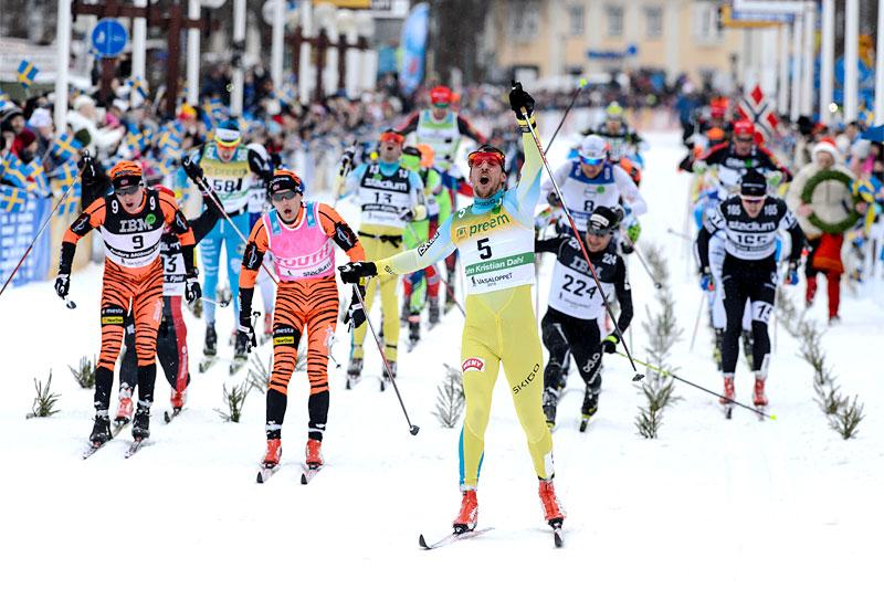 John Kristian Dahl strekker armene i været som vinner av Vasaloppet 2016 etter å ha avgjort det intense bikkjeslagsmålet det var i rennets sluttfase. Foto: Rauschendorfer/NordicFocus.