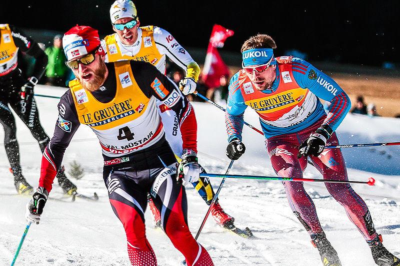 Martin Johnsrud Sundby leder foran Sergey Ustiugov underveis på fellesstarten i Val Müstair, 2. etappe i Tour de Ski 2016-2017. I mål var rekkefølgen snudd. Foto: Modica/NordicFocus.