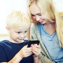 Liten gutt og stor jente med mobil (Foto: Medietilsynet)