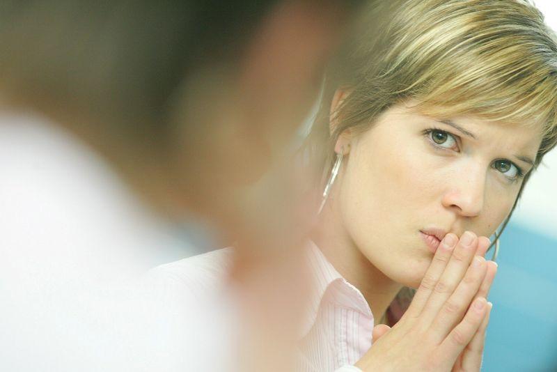Bilde av to personer, hvor den i forgrunnen er ute av fokus og kvinnen i bakgrunnen har holder hendene sammen foran munnen og ser forsiktig på personen foran seg.