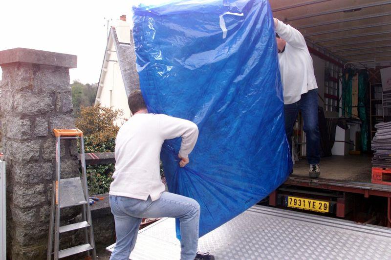 Bilde av bakdørene til en lastebil hvor to menn løfter inn noe stort firkantet pakket inn i blå plass