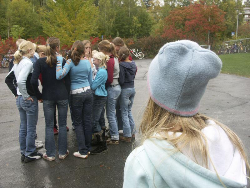 Bildet er av ei gruppe ungdommer hvor ei jente står utenfor