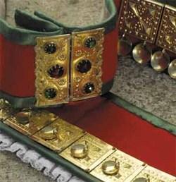 <br><i>Detaljar av beltet med den flotte spenna. Heilt i forkant ligg underbindinga til kruna med kniplingskant</i>