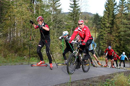 Andreas Molden fører an for hele landslaget. Trener Steinar Mundal sykler. Sjur Røthe følger nærmest nesbuen. I rødt sees Petter Northug jr. Foto: Erik Borg.