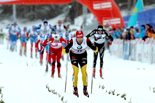 Tyskeren Axel Teichmann gikk klar av Dario Colognas fall like før oppløpet i jaktstarten på 2. etappen av Tour de Ski og kunne stake rolig inn til seier. Bak ser vi Petter Northug og Dario Cologna kjempe om 2. plass. Foto: Hemmersbach/NordicFocus.