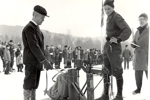 Erling Riddervold kontrollerer vekt på sekken i 1950. Johan Haanes er eier av sekken. Eystein Raabe er funksjonær. Arrangørfoto.