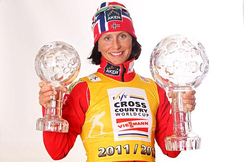 Marit Bjørgen med de synlige bevisene på at hun i sesongen 2011/2012 vant verdenscupens distansecup og også tok sammenlagtseieren. Foto: Hemmersbach/NordicFocus.