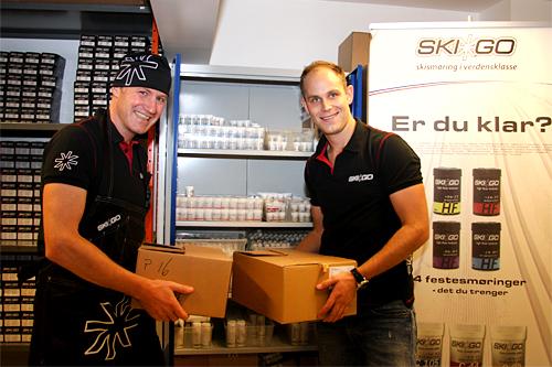 André Borka (til venstre) og Henrik Kvissel jobber begge hos Sportalen AS, som blant annet fører Skigo-produkter og ernæring fra Winforce. Her er det Skigo-smøring som pakkes og sendes. Foto: Geir Nilsen/Langrenn.com.