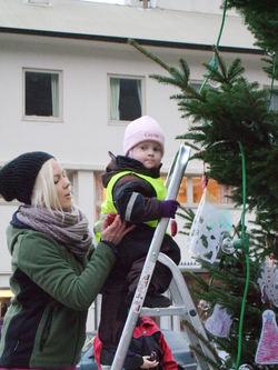 Guro Omdal henger opp juletrepynt sammen med Evy Alice Moi