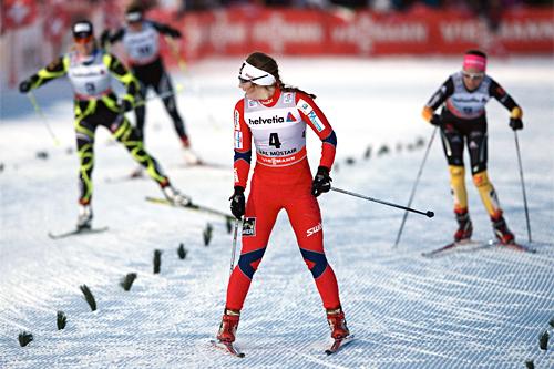 Ingvild Flugstad Østberg bremser opp i semifinalen på 3. etappe av Tour de Ski 2012-2013 for å gi finaleplass til Kristin Størmer Steira i Val Müstair og Sveits. Foto: Felgenhauer/NordicFocus.