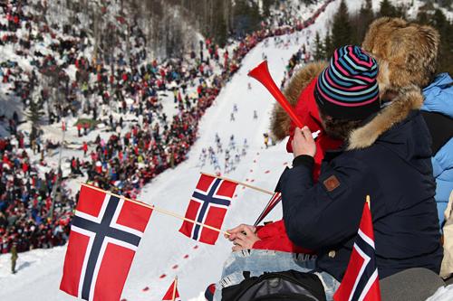 Feltet i 5-mila under VM i Holmenkollen i 2011 er nede i bakken, tett omkranset av stort publikum og norske flagg. Foto: Hemmersbach/NordicFocus.