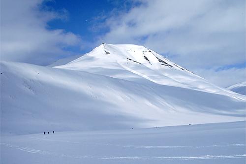 De små sorte prikkene i nedre venstre hjørne er deltakere i Svalbard Skimaraton. Som man ser, naturen er både mektig og storslått. Foto: Kirsti Kringhaug/Langrenn.com.