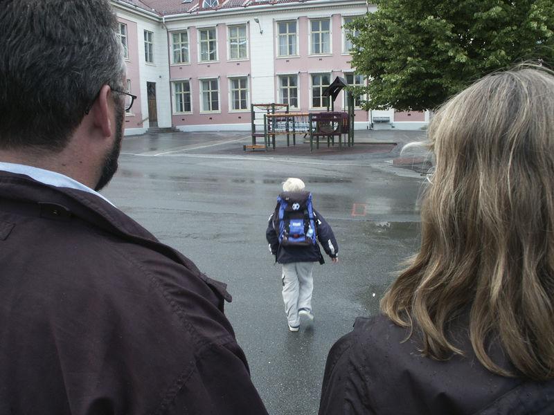Foreldre og sønn foran skole