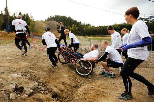 Cato Ulvestad med sitt følge på vei mot toppen ved Tryvannstårnet i rullestol under en tidligere utgave av motbakkeløpet Oslos Bratteste opp Wyllerløypa. Foto: Oslos Bratteste.