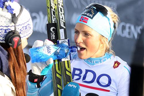 Therese Johaug gjorde som i fjor og gikk helt til topps i sesongens første renn i Beitosprinten 2013. Seieren feiret hun med NRK-intervju og en flaske vann fra Isklar. Foto: Geir Nilsen/Langrenn.com.