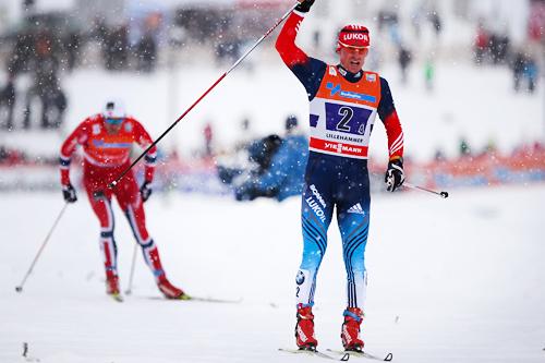 Maxim Vylegzhanin avgjør verdenscupstafetten på Lillehammer 2013. Bak i bildet følger Petter Northug jr. for Norge I, som gikk inn til 3. plass etter Finn Hågen Krogh for Norge II. Foto: Laiho/NordicFocus.