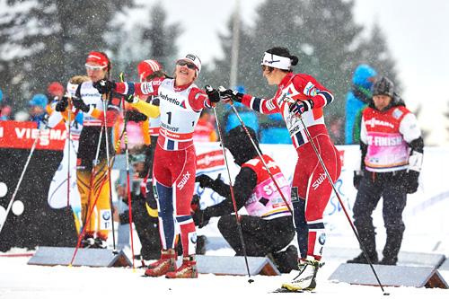 Marit Bjørgen, nærmest kamera, og Ingvild Flugstad Østberg står på startstreken under 2. etappe i Tour de Ski i Oberhof i desember 2013. Foto: Felgenhauer/NordicFocus.