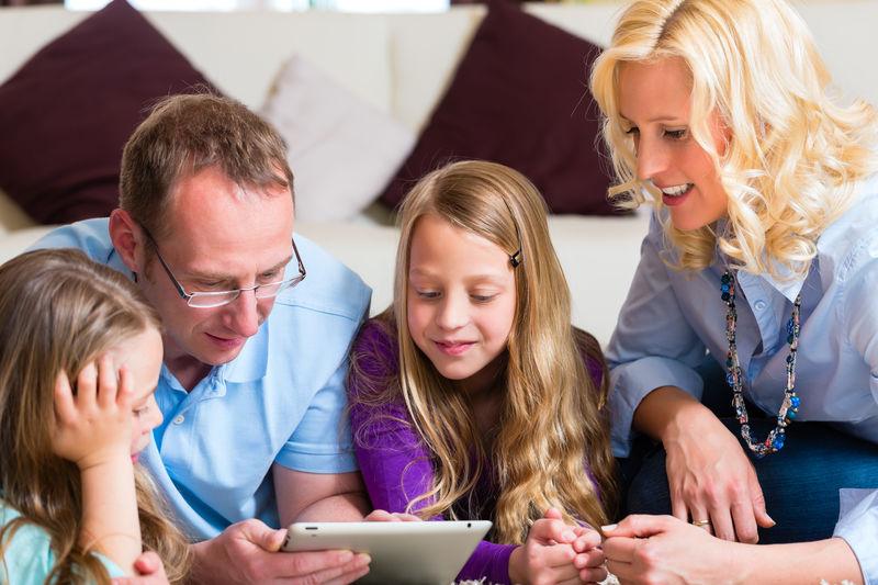 Foreldre og barn på nettbrett