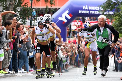 Eldar Rønning drar på Østensen, Pettersen og Northug i Toppidrettsveka 2014, mens de er på vei opp den lange og stupbratte bakken på Bakklandet i sentrum av Trondheim. Foto: Geir Nilsen/Langrenn.com.