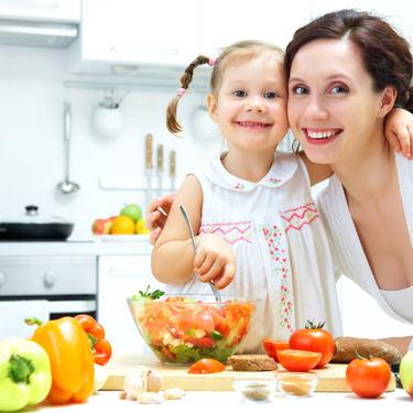 Barn og mor som lager sunn mat, helse og ernæring
