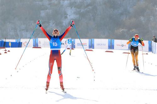 Sofie Nordsveen Hustad strekker armene i været som vinner av 10 km skiathlon under Junior-VM 2015 i Almaty og Kasakhstan. Bak til høyre følger sølvvinner Victoria Carl fra Tyskland. Foto: Erik Borg.