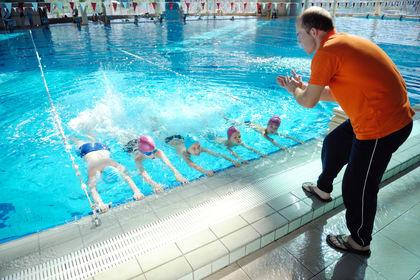 Barn i basseng får svømmeopplæring