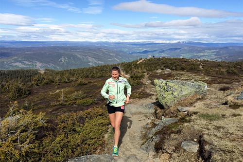 Skiløper Marthe Bjørnsgaard i løypa for Hafjell Opp. Her ved løpets høyeste punkt, Hafjelltoppen, 1065 meter over havet. Jotunheimen og fakkelmannen i bakgrunnen. Foto: Hafjell Opp.