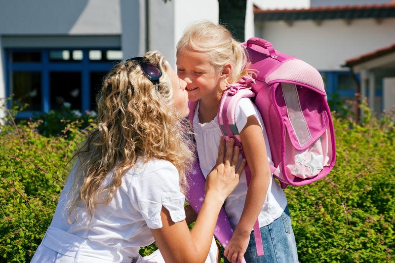 Skolejente med rosa sekk og mamma