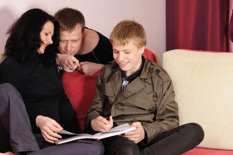 Tenåring og foreldre samtaler over bok