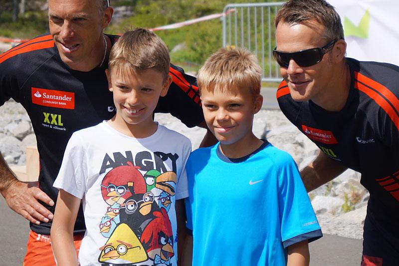 Anders og Jørgen Aukland sammen med unge skiløpere i forbindelse med Sommarland Skifestival og sommerskiskolen i Bø. Arrangørfoto.