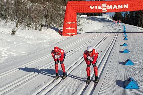 Mihhail Lukertsenko (til venstre i bildet) og Morten Sætha, begge inngår i Swix sin racingservice, tester ski foran et tidligere renn i verdenscupen. Foto: Swix.