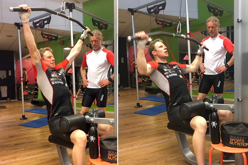 Her gjør Petter Soleng Skinstad nedtrekk til bryst med bredt grep, mens Åge Skinstad følger med på øvelsen. Foto: Odd Christian Hagen/Toten Treningssenter.