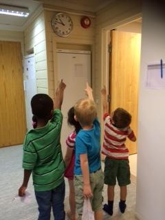 Barn peker på alarmklokke