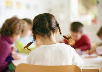 Jente bakfra med musefletter i klasserom