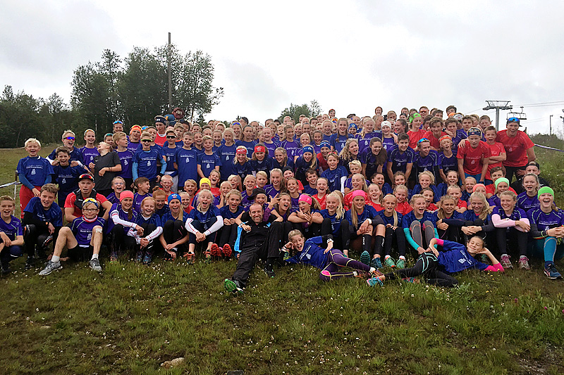 Odd-Bjørn Hjelmeset sammen med deltakere i Odd-Bjørn Hjelmeset Bendit Sommerskiskole. Arrangørfoto.