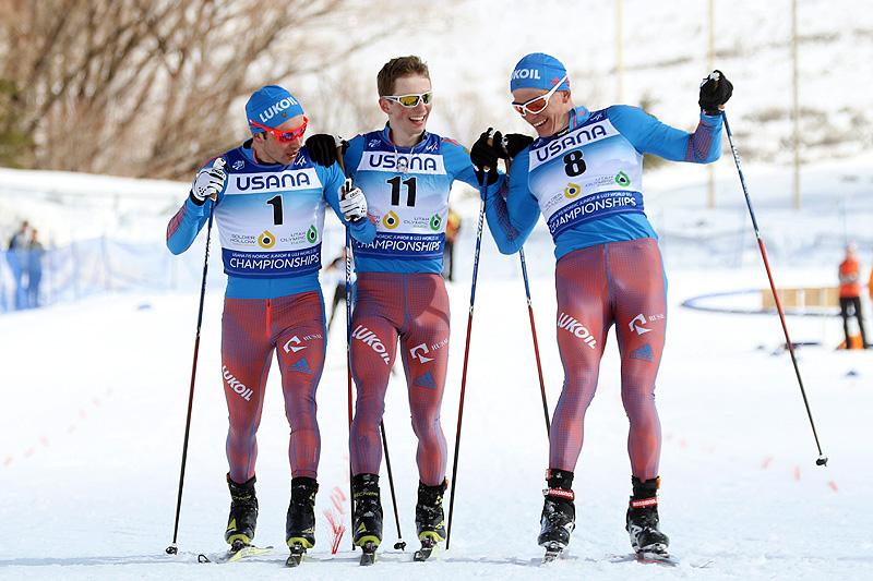 Alexey Chervotkin (f.v.), Alexander Bolshunov og Denis Spitsov krysser målstreken sammen i et forsøk på å dele gullet på skiathlon under U23-VM i Park City 2017. Juryen bestemte at Bolshunov gikk i mål først, foran Chervotkin og Spitsov. Foto: Erik Borg.