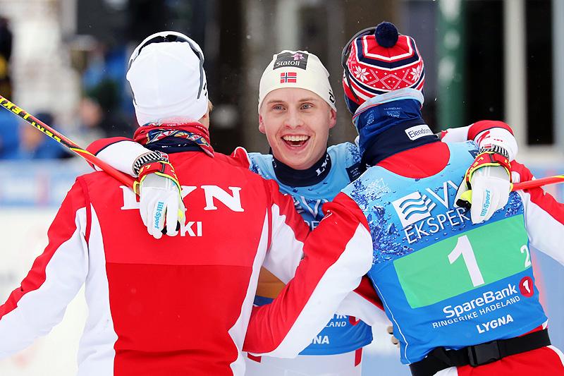Simen Hegstad Krüger gikk ankeretappen for Lyn Ski, som vant stafettgull under NM på Lygna 2017, og omfavnes her av lagkameratene Johan Tjelle og Hans Christer Holund. Foto: Eirik Lund Røer/Eiluro.