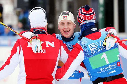 Simen Hegstad Krüger gikk ankeretappen for Lyn Ski, som vant stafettgull under NM på Konnerud 2020. Bildet er fra Lygna-NM 2017 hvor Simen ble omfavnet av de samme lagkameratene, Johan Tjelle og Hans Christer Holund, som nå. Foto: Eirik Lund Røer/Eiluro.