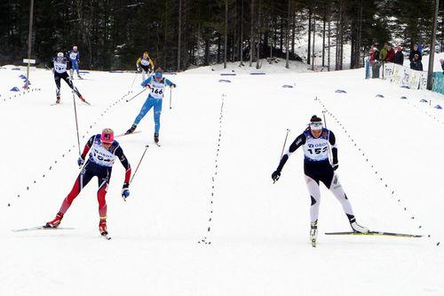 Marte Mæhlum Johansen fra Oppland (t.v.) krysser målstreken like foran Kristine Stavås Skistad fra Buskerud i kretsstafetten under Junior-NM i Harstad 2017. Foto: Erik Borg.