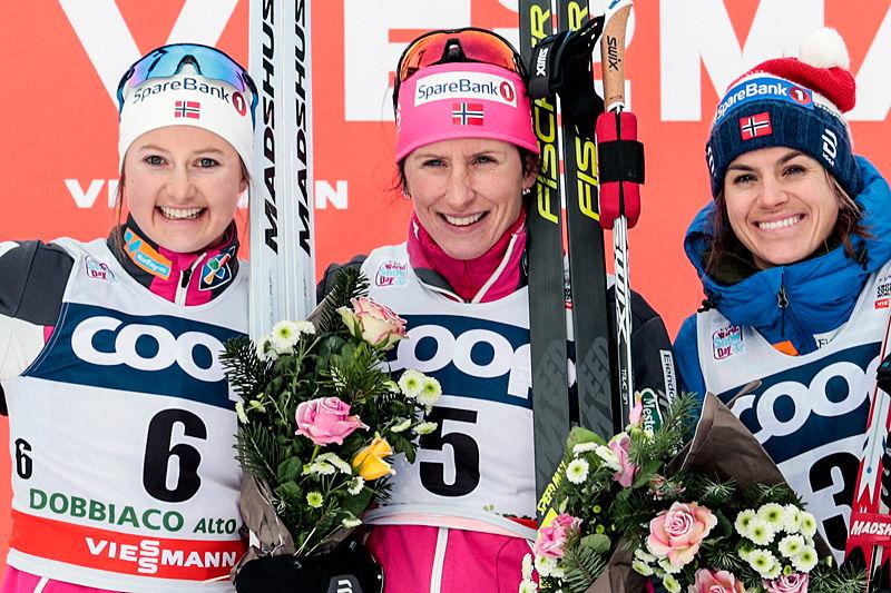 Seierspallen etter damenes 10 kilometer lange jaktstart i klassisk stil under verdenscupen i Toblach 2017. Fra venstre: Ingvild Flugstad Østberg (2. plass), Marit Bjørgen (1) og Heidi Weng (3). Foto: Modica/NordicFocus.