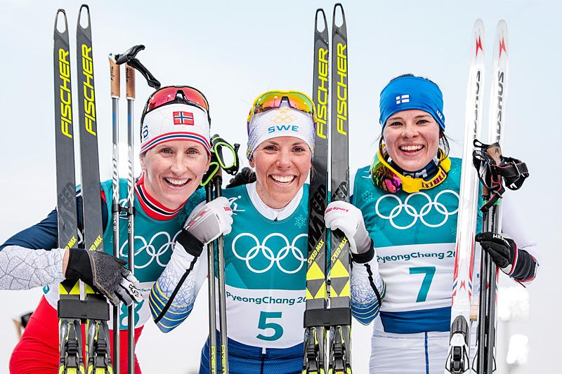 Seierspallen etter 15 km skiathlon under OL Pyeongchang 2018. Fra venstre: Marit Bjørgen (sølv), Charlotte Kalla (gull) og Krista Pärmäkoski (bronse). Foto: Modica/NordicFocus.